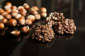 Chocolate pieces with nuts on black background — Stock Photo