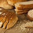 Wheat Bread, wheat seeds and bread slices with wooden background — Stock Photo #69355947