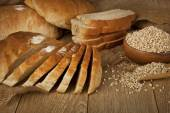 Wheat Bread, wheat seeds and bread slices with wooden background — Stock Photo