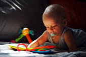 Baby with pacifier, books and toys. — Stock Photo
