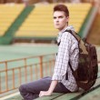 Handsome young pensive man with backpack, modern hipster sitting — Stock Photo #52914853