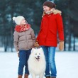 Beautiful happy family, mother and son walking with white Samoye — Stock Photo #52918819
