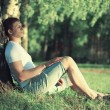 Pensive man sitting near a tree with his eyes closed meditating  — Stock Photo #52919411