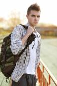 Outdoor lifestyle portrait of handsome guy with backpack — Stock Photo