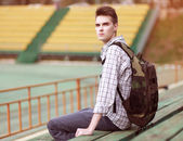 Handsome young pensive man with backpack, modern hipster sitting — Stockfoto
