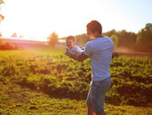 Happy child, dad and son having fun, holding on hands on a sunse — Stock Photo