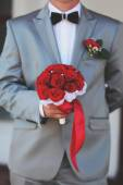Groom holding bridal bouquet — Stock Photo