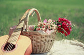 Guitar, basket and bouquet of flowers. Vintage tender background — Stock Photo