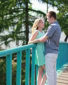 Pretty happy couple on the bridge in love — Stock Photo