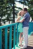 Romantic happy couple in love kiss on the bridge — Stock Photo