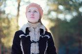 Porträtt söt ung flicka i jacka och basker i skogen — Stockfoto