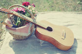 Guitar, basket with wine and bouquet of flowers. Vintage tender  — Stock Photo