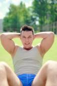 Fitness outdoors, sportsman doing abdominal exercises — Stock Photo