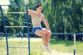 Street workout, handsome sporty guy on horizontal bars — Stock Photo