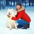 Happy smiling woman with Samoyed dog walking in winter park — Stock Photo #56213139