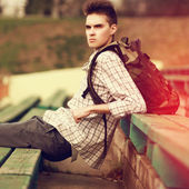 Fashion lifestyle portrait of handsome hipster man with backpack — Stock Photo