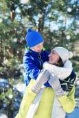 Child hugs his mom and have fun together in winter, sunny snowy — Stock Photo