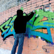 Yaroslavl, Russia - March 05, 2008: man in black paints graffiti — Stock Photo #67598673