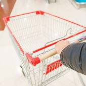 Hand and shopping trolley — Stock Photo