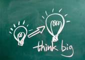 Think big and light bulb on blackboard — Stock Photo