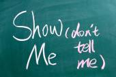Show Me, Don't Tell Me written by hand on a used blackboard — Stock Photo