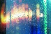 Wet window with night city — Stock Photo