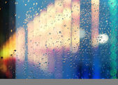 Wet window with the background of the night city — Stock Photo