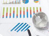 Globe and chart on desk — Stock Photo
