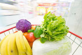 Shopping cart  filled with the fruits and vegetables — Stock Photo
