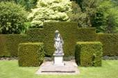 Woman statue on a plinth in a garden — Stock Photo