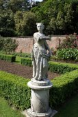 Statue of a woman holding a flower in a garden, Cliveden, Buckinghamshire, England — Stock Photo