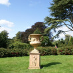 Sculptured urn on a plinth in a garden — Stock Photo #64017453