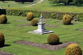 Child statue in a topiary garden — Stock Photo