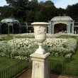Sculptured urn on a plinth in front of a garden & an aviary — Stock Photo #75514323