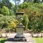 Sculptured urn on a plinth in a garden — Stock Photo #78884556