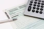 Form of income tax return with ball pen and pocket calculator — Stock Photo