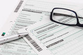 Form of income tax return with ball pen and glasses — Stock Photo