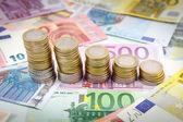 Decreasing stacks of euro coins on euro banknotes — Stock Photo