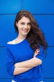 Portrait of young naughty beautiful brunette woman with blue geometric background — Stock Photo