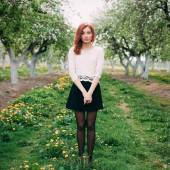 Full length portrait of a young cute redhead woman in a apple orchard — Stock Photo