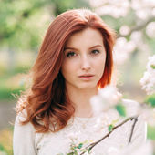 Portrét ženy mladá krásná rusovláska v rozkvetlé zahradě — Stock fotografie