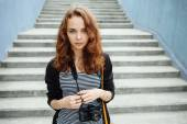 Young hipster woman with a vintage film camera on the stairs — Stock Photo
