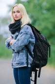 Outdoors portrait of a young beautiful blonde woman in jeans with a big old backpack — 图库照片