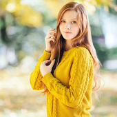 Autumn portrait of a young cute redhead woman in yellow sweater — Stock Photo