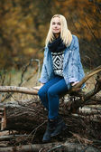Young serious beatiful blonde woman in jeans, scarf, and sweater, posing in autumn background — Stock Photo