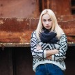Young cute blonde woman in sweater, scarf, and jeans outdoors portrait with abandoned grunge background — Stock Photo #59326481
