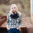 Young cute blonde woman in sweater, scarf, and jeans outdoors portrait with abandoned grunge background — Stock Photo #59326397