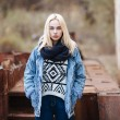 Young serious blonde woman in sweater, scarf, and jeans outdoors portrait with abandoned grunge background — Stock Photo #59326405