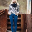Young cute blonde woman in sweater, scarf, and jeans outdoors portrait with abandoned grunge background — Stock Photo #59326425