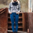 Young cute blonde woman in sweater, scarf, and jeans outdoors portrait with abandoned grunge background — Stock Photo #59326427